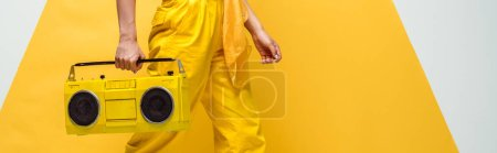 Photo for Panoramic shot of young woman holding retro boombox on white and yellow - Royalty Free Image