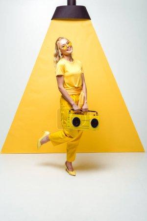 Photo pour Femme gaiposant avec le boombox rétro sur le blanc et le jaune - image libre de droit
