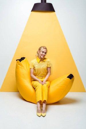 Photo pour Heureuse femme blonde assise sur une chaise de sac de haricot sur blanc et jaune - image libre de droit
