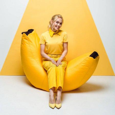 Photo pour Femme blonde gaie assise sur une chaise de sac de haricot sur blanc et jaune - image libre de droit