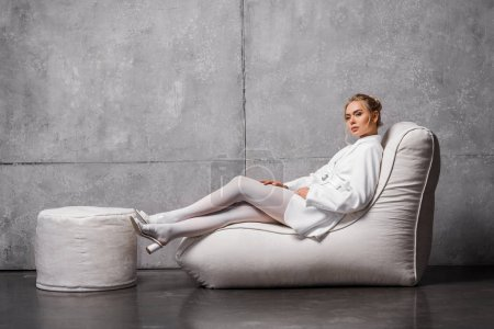 attractive blonde woman sitting on soft bean bag chair on grey