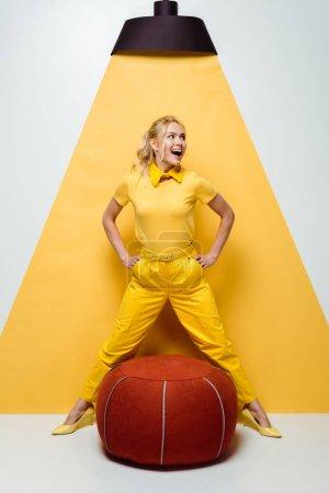 Photo pour Joyeuse fille blonde posant avec les mains sur les hanches près de tabouret rembourré rouge sur blanc et jaune - image libre de droit