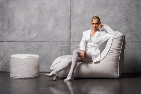 Foto de Pensive young woman sitting on soft bean bag chair on grey - Imagen libre de derechos