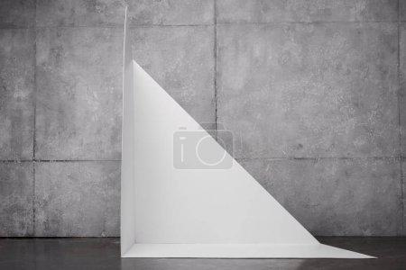 triangle shape carton near grey wall with copy space