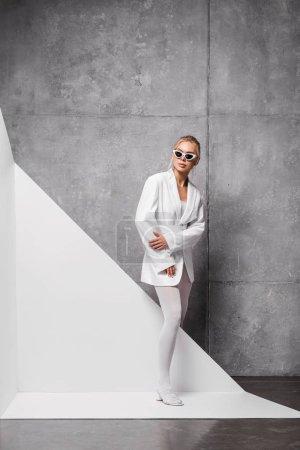 Photo pour Femme séduisante et élégante en lunettes de soleil posant sur blanc et gris - image libre de droit