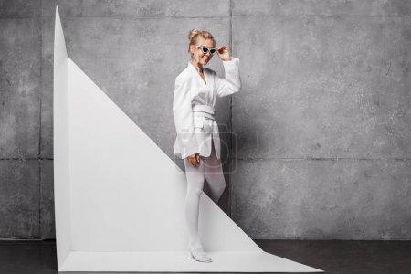 Photo pour Femme heureuse et élégante touchant lunettes de soleil et posant sur blanc et gris - image libre de droit