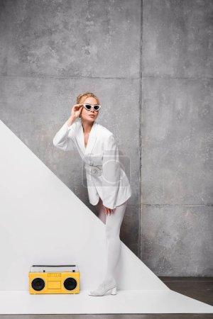 Photo pour Femme élégante dans des lunettes de soleil posant près de boombox jaune rétro sur blanc et gris - image libre de droit