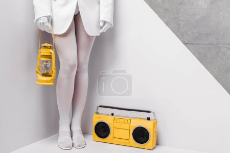 Photo pour Vue recadrée de femme posant près de boombox rétro et retenant la lampe jaune de cru sur le blanc et le gris - image libre de droit