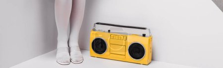 Photo for Panoramic shot of woman posing near retro yellow boombox on white - Royalty Free Image