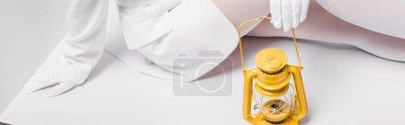 Photo pour Plan panoramique de jeune femme assise avec une lampe rétro jaune sur blanc - image libre de droit