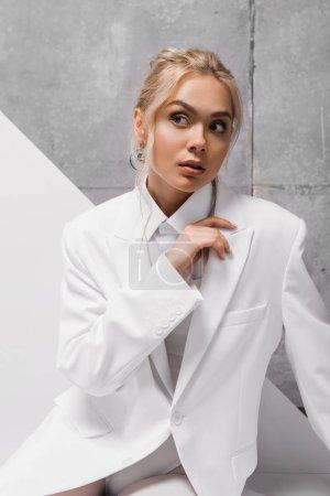 Photo pour Attrayant et à la mode jeune femme blonde sur blanc et gris - image libre de droit