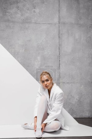 atractiva joven rubia sentada en blanco y gris