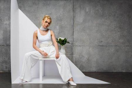 Photo pour Femme attirante et élégante s'asseyant près du vase avec des fleurs sur le blanc et le gris - image libre de droit