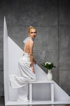 Photo pour Femme blonde élégante posant près du vase avec des fleurs sur le blanc et le gris - image libre de droit