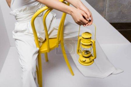 vue recadrée de la jeune femme assise sur une chaise jaune et tenant une lampe rétro sur blanc et gris