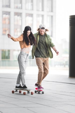 Photo for Happy couple in casual wear riding on skateboards in city - Royalty Free Image