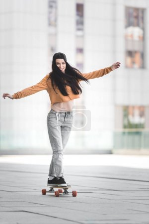 Foto de Brunette woman with outstretched hands looking at camera, riding on skateboard in city - Imagen libre de derechos