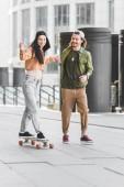 "Постер, картина, фотообои ""happy woman holding hands with handsome man, riding on skateboard in city"""