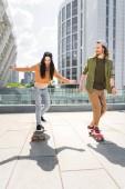 """Постер, картина, фотообои """"happy couple in casual wear riding on skateboards on roof"""""""
