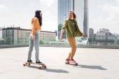 "Постер, картина, фотообои ""man in casual wear looking at brunette woman, riding on skateboard on roof"""