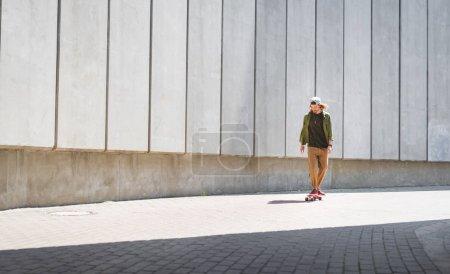 Photo pour Homme adulte conduisant sur la planche à roulettes près du mur en béton - image libre de droit