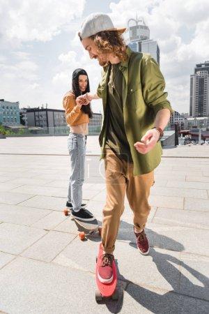Photo pour Foyer sélectif de l'homme joyeux tenant la main avec une femme, chevauchant sur des planches à roulettes sur le toit - image libre de droit