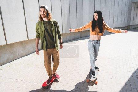 Photo pour Vue d'angle élevé de l'homme et de la femme avec les mains tendues équitation sur la planche à roulettes près du mur en béton - image libre de droit