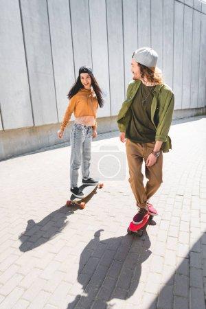 Photo pour Vue grand angle de femme heureuse et l'homme en tenue décontractée équitation sur planche à roulettes près du mur de béton - image libre de droit