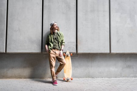 Photo for Handsome man in casual wear standing near concentrate wall and skateboard, looking away - Royalty Free Image