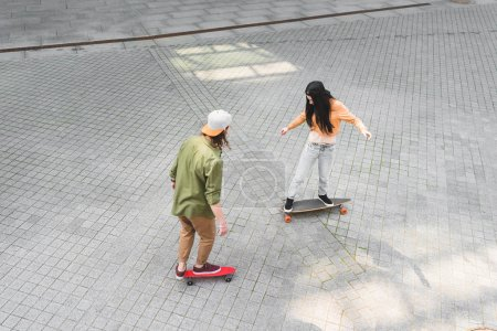 Photo for High angle view of two friends riding on skateboards at street - Royalty Free Image