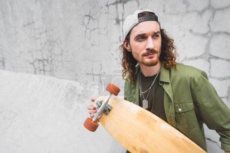 Photo pour Homme calme regardant loin, debout près du mur avec planche à roulettes - image libre de droit