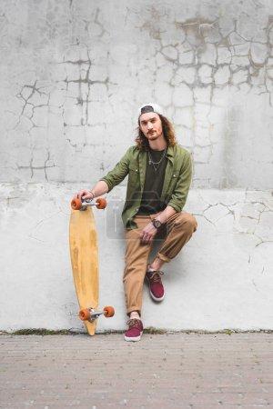 Photo pour Homme confiant en tenue décontractée regardant la caméra, debout près du mur avec planche à roulettes à la main - image libre de droit