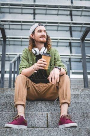 vue à angle bas de l'homme heureux avec tasse en papier à la main regardant loin, assis sur les escaliers