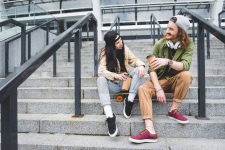 low angle view of woman and man sitting on skateboard with paper cup in hands, looking at each other