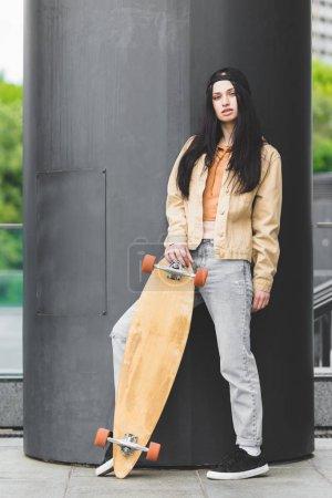 Photo pour Femme brune calme avec la planche à roulettes restant sur le toit, regardant l'appareil-photo - image libre de droit