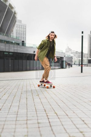 Photo for Handsome and calm man in casual wear riding on skateboard, looking away - Royalty Free Image