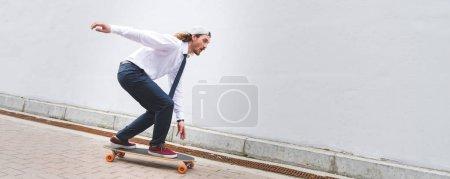 Photo pour Vue panoramique de l'homme d'affaires beau conduisant sur la planche à roulettes à la rue - image libre de droit