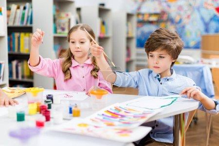 Photo pour Gosses mignons retenant des brosses à peinture colorées bocaux et papiers de gouache - image libre de droit