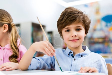Photo for Happy kid holding paintbrush near child and looking at camera - Royalty Free Image