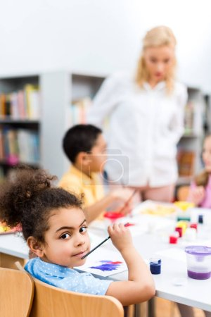 Photo pour Selective focus of cute black girl looking at camera near kids and woman - image libre de droit