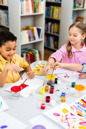Photo pour Foyer sélectif des enfants multiculturels heureux peignant sur des papiers - image libre de droit