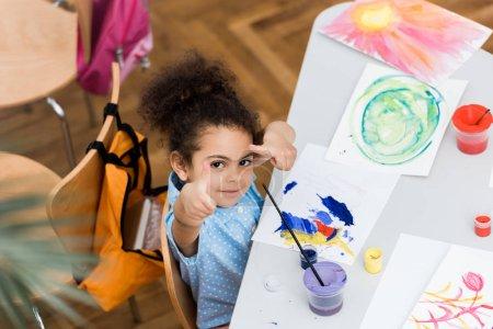 Photo pour Vue au-dessus de la vue mignonne d'enfant américain africain mignon pointant avec des doigts près du papier avec la peinture - image libre de droit
