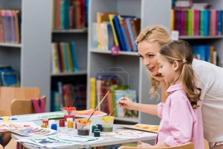 Photo pour Professeur attrayant près de la peinture mignonne d'enfant sur le papier dans la bibliothèque - image libre de droit