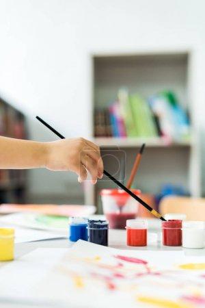 Photo pour Vue recadrée de l'enfant retenant le pinceau près des bocaux de gouache - image libre de droit