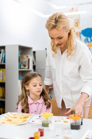 Photo pour Selective focus of beautiful woman standing near cute kid and looking at papers with drawing - image libre de droit