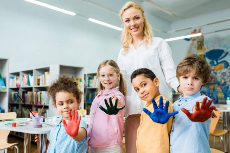 Photo pour Selective focus of cheerful woman standing with multicultural kids showing colorful hands with gouache paint - image libre de droit