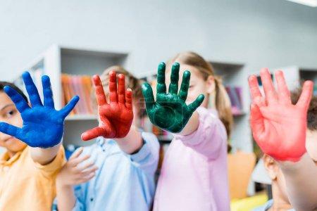 Photo pour Foyer sélectif des enfants multiculturels couvrant des visages avec des mains colorées - image libre de droit
