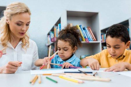 Foto de Selective focus of woman sitting near african american kids with color pencils - Imagen libre de derechos
