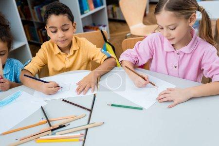 Photo pour Enfants multiculturels mignons dessinant sur des papiers avec des crayons de couleur - image libre de droit