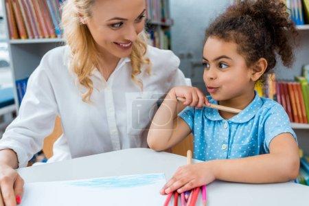 Photo pour Foyer sélectif de la femme gaie regardant l'enfant américain africain heureux - image libre de droit